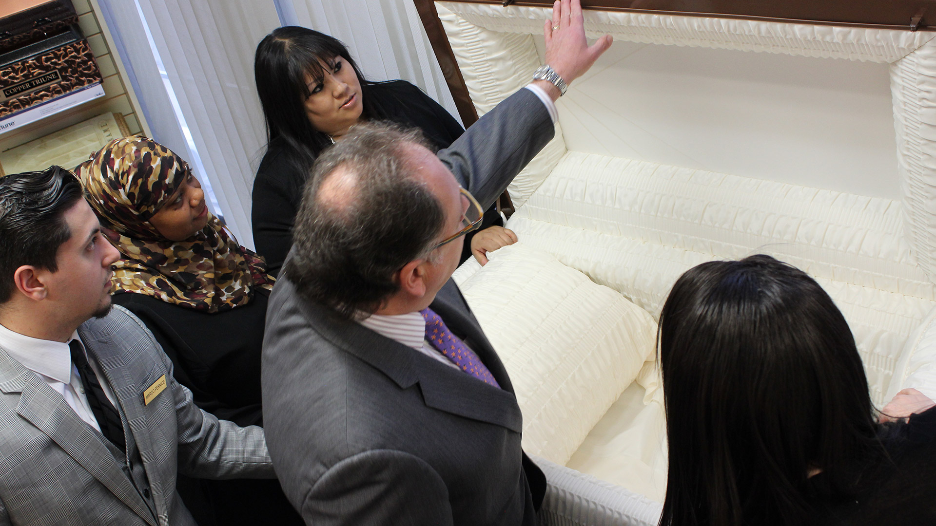 Funeral service students study the inside of a casket