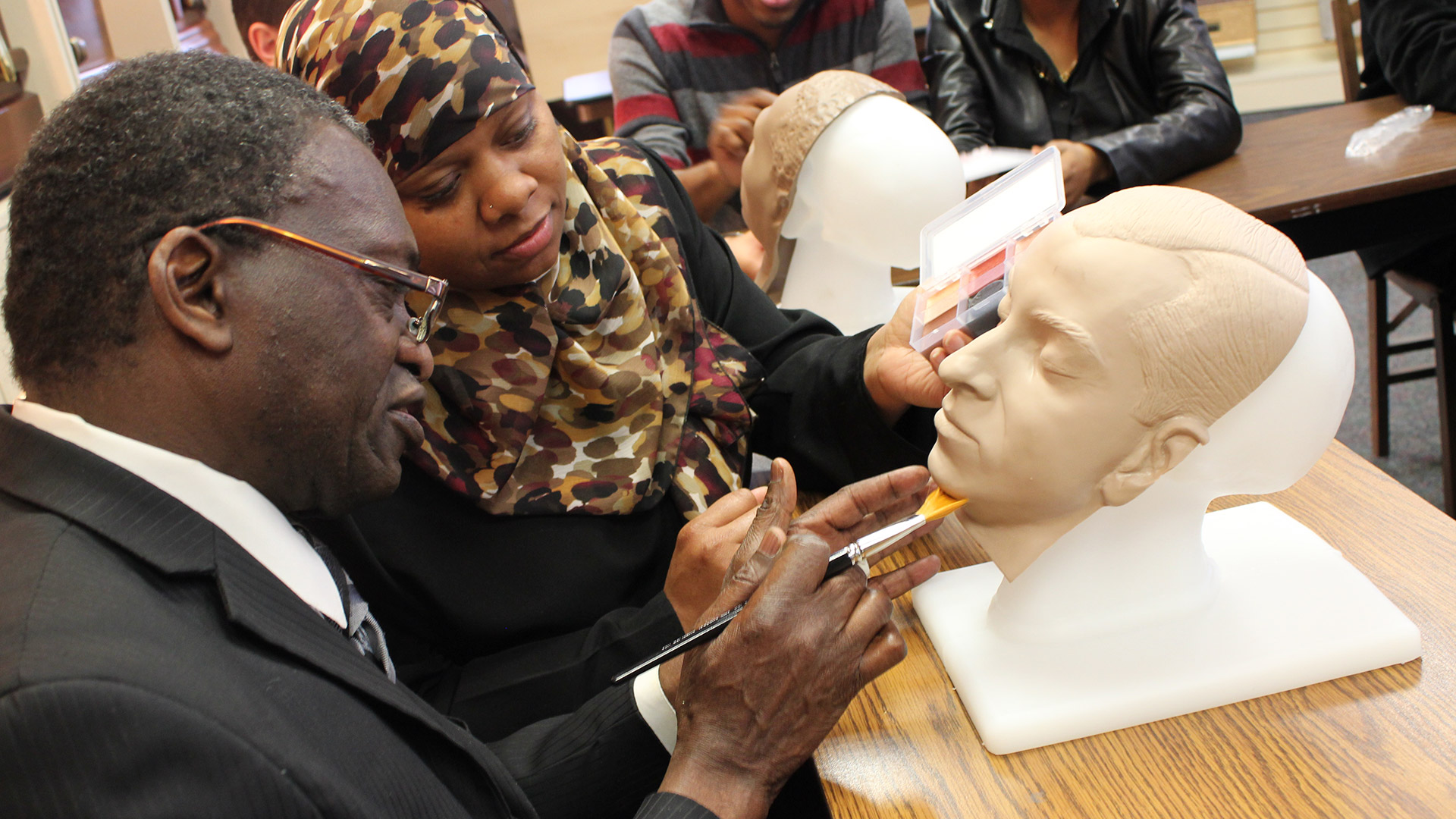 Funeral service students practice applying color to mannequin heads