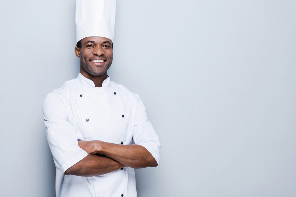 Culinary student smiles in uniform in front of white wall