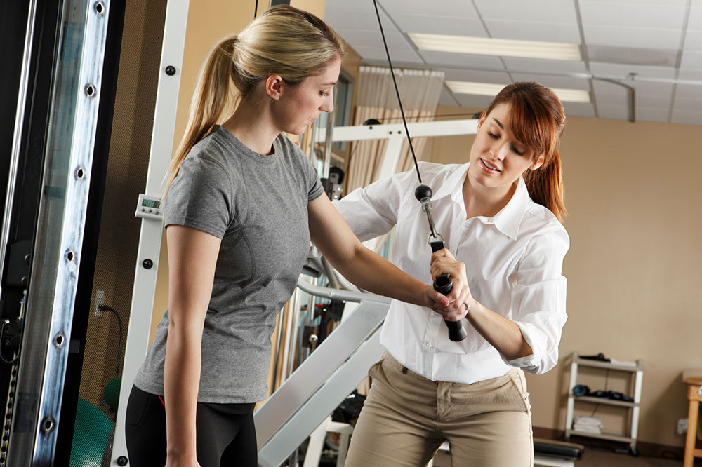 Occupational Therapy Assistant helps patient use machine to improve muscle strength