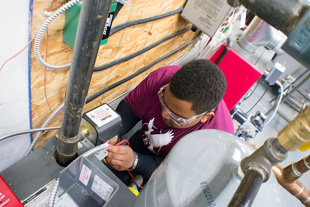 HVAC student practices using machine connected to pipe