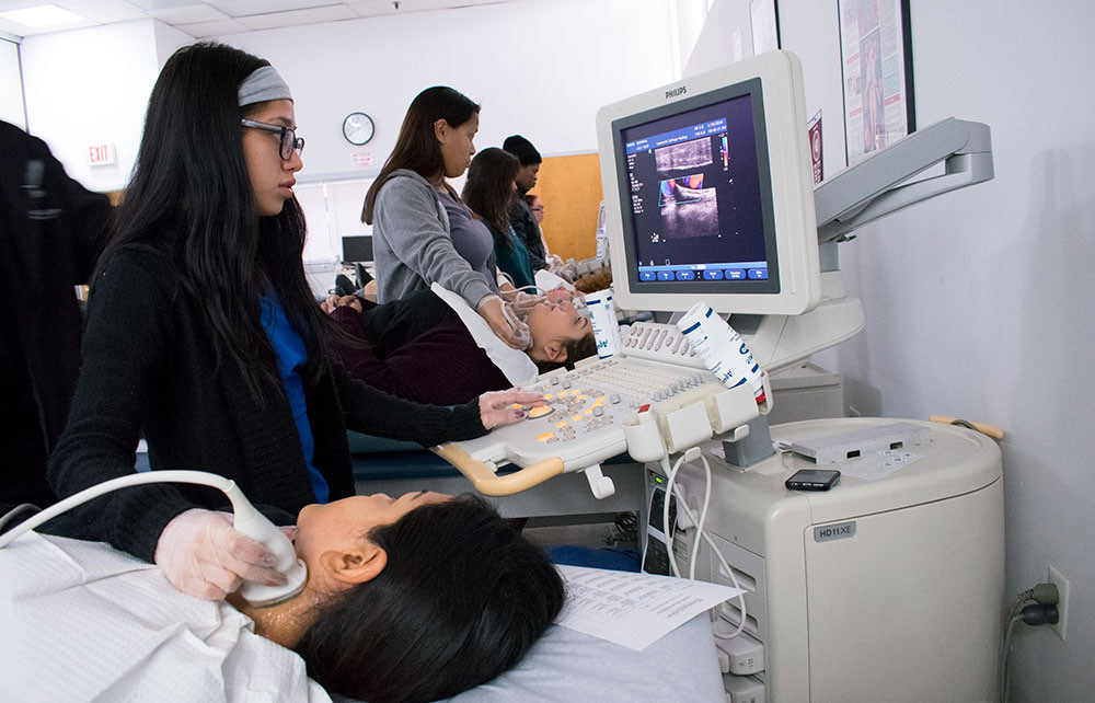 Cardiovascular students practice using ultrasound machine on fellow students