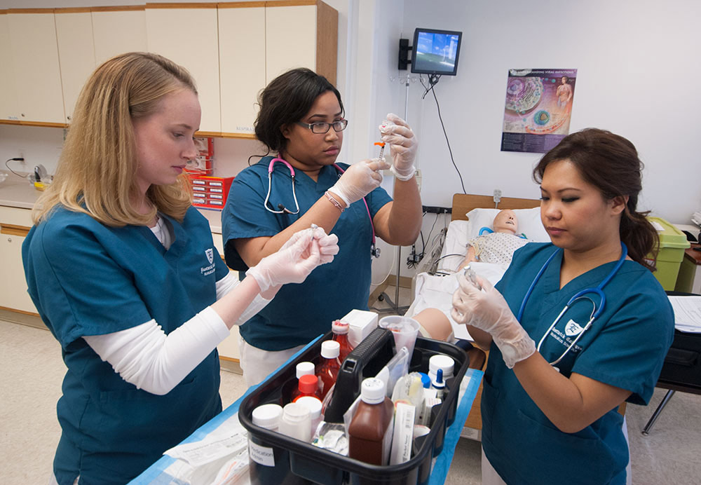 LPN program students practice taking liquid out of bottles using syringes