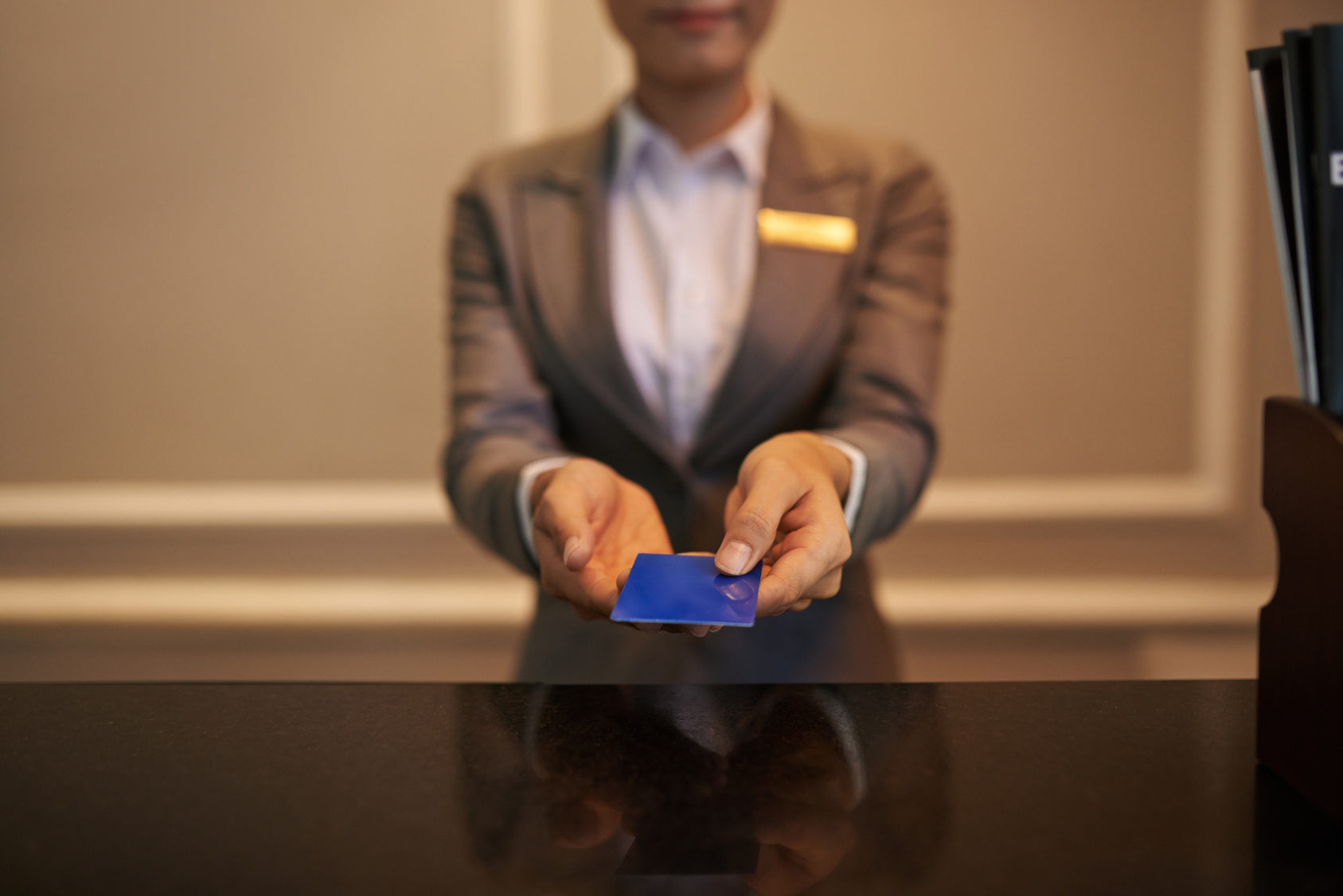 Hotel staff member handing key card to camera