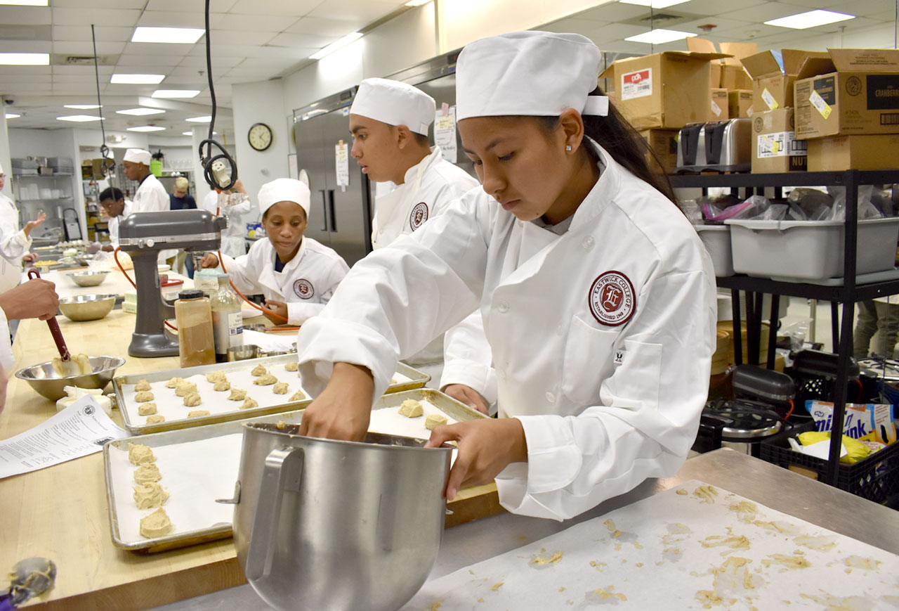Culinary program students measure out balls of dough onto baking sheet