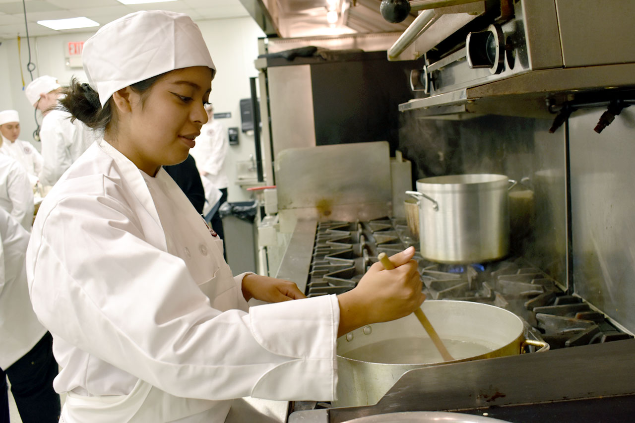 Culinary program student stirs pot in kitchen