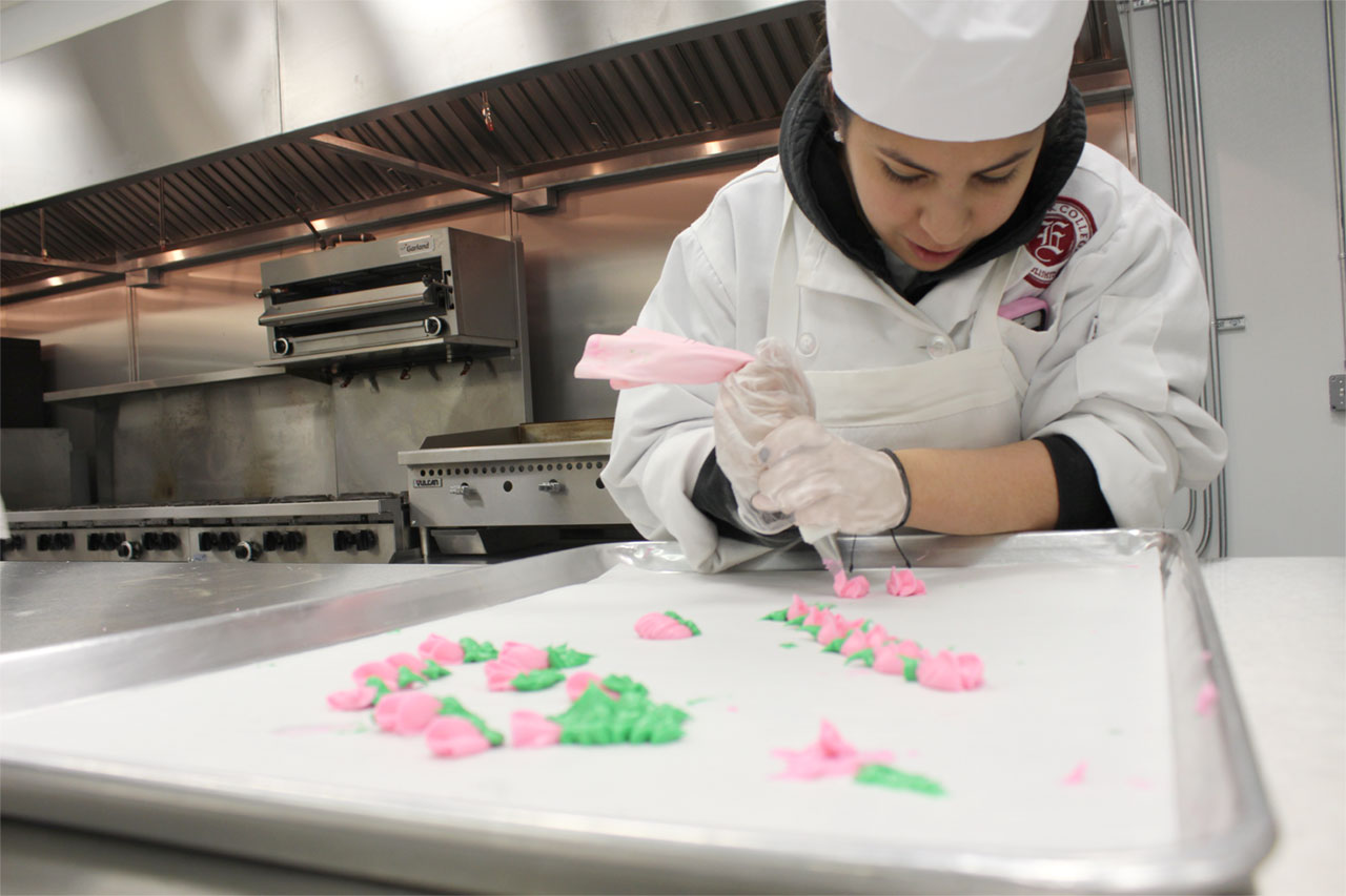 Culinary program student pipes flowers made of frosting onto baking sheet
