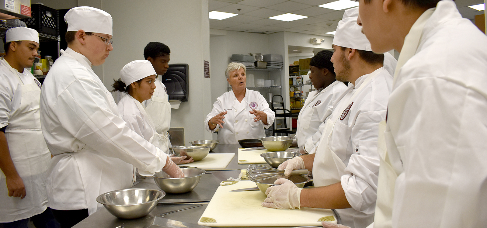 Culinary Arts Associates students stand around table full of kitchen tools listening to instructor