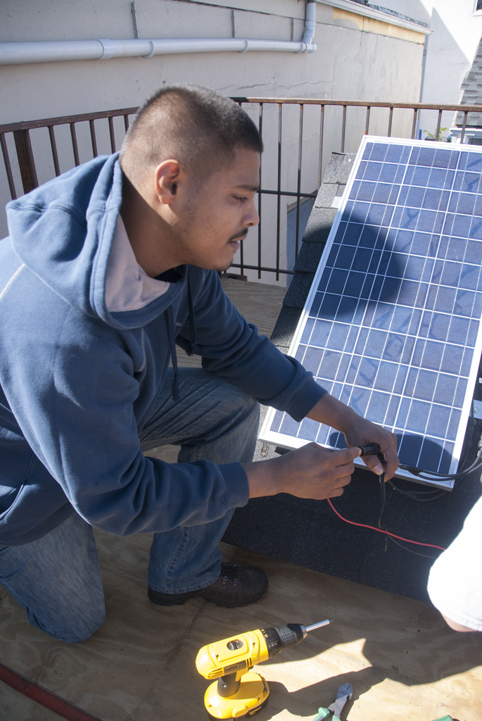 Construction training student practices setting up solar panel