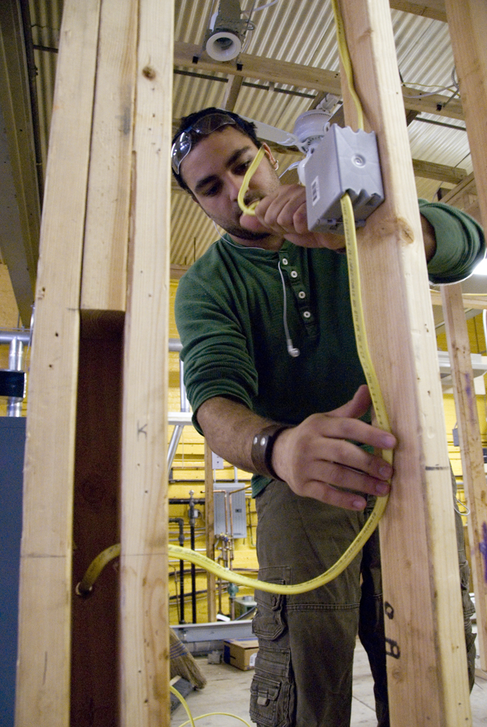 Construction training program student measures beam of wood
