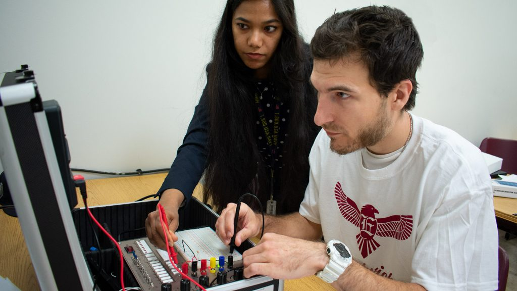 IT students practice measuring electric flow in device