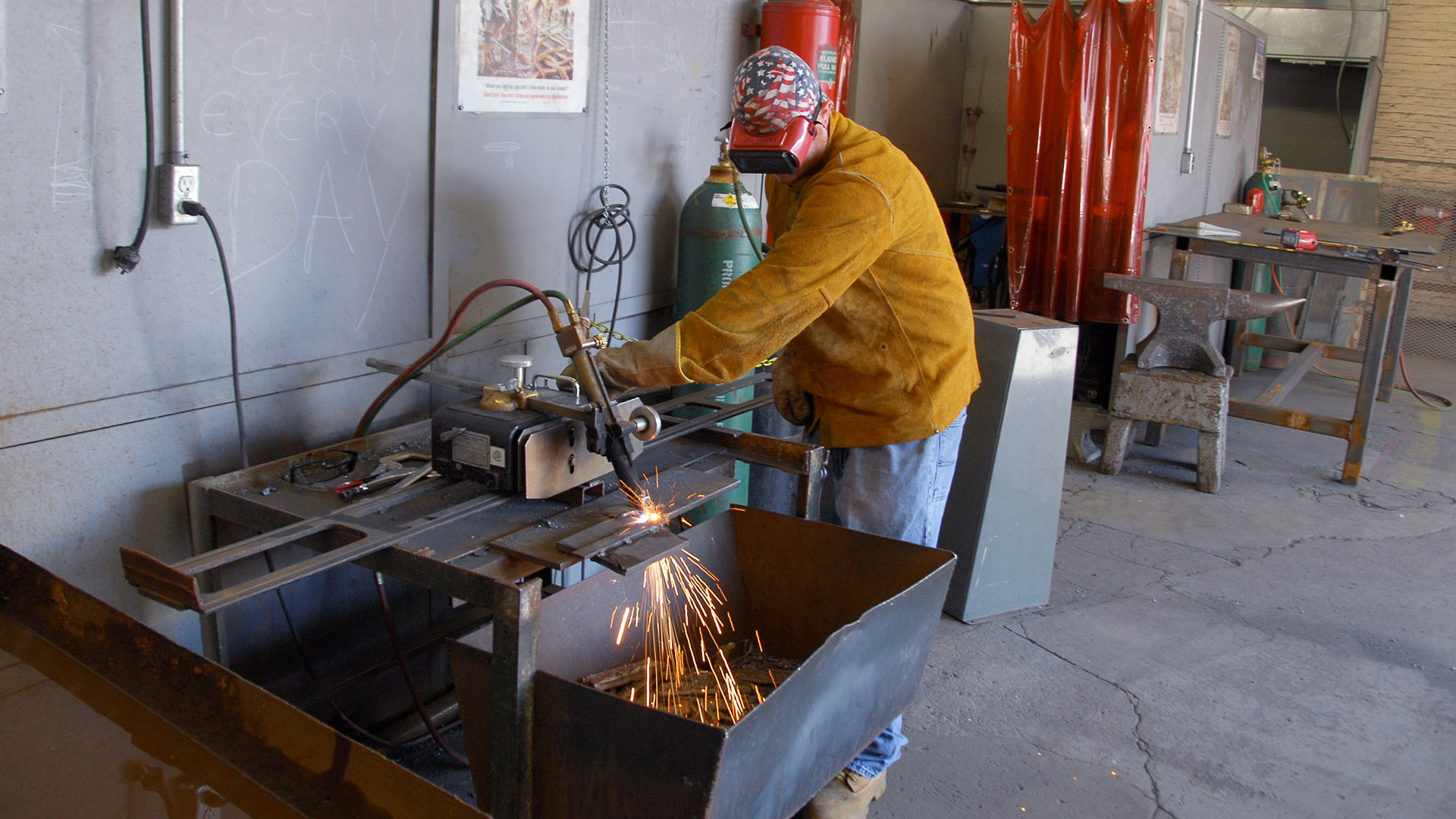 Welding student practices cutting metal in workshop with sparks flowing