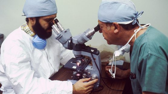 surgical technician and professor looking into microscope