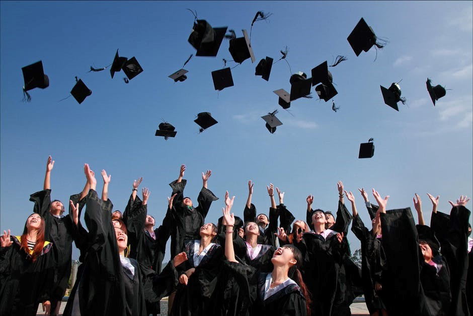 newly graduated students celebrate by tossing their caps into the air