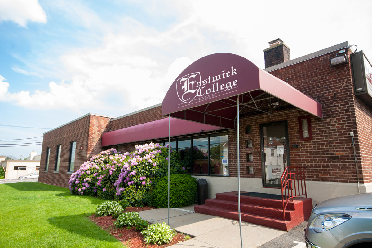Front door of eastwick college in nutley with awning and flowers