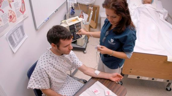 medical student practices taking blood on volunteer