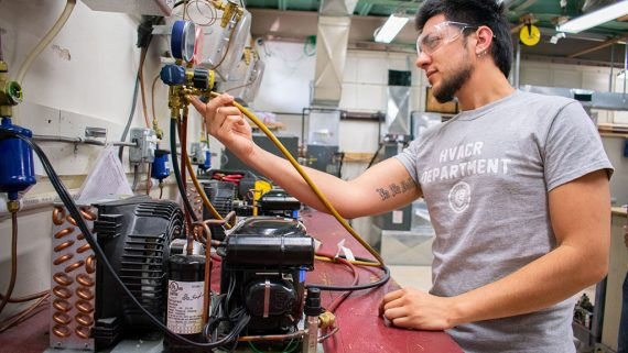 hvac student practices adjusting temperature on air conditioning machine