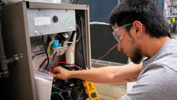 hvac student practices wiring air conditioning unit