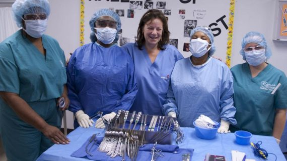 Medical students pose with instructor in front of table full of medical tools