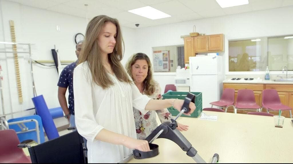 occupational therapist students practice using tool to increase muscle strength